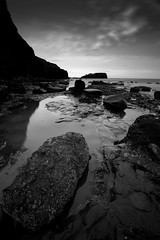 Darth (Nick JH) Tags: blackandwhite bw seascape clouds dark rocks moody gloomy grim canon5d bandw rockybeach slowshutterspeed landsape movingclouds blackandwhitelandscape