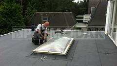 Dakdekker: Totaalplaatje van het platte dak 80 m2 dat is voorzien van een nieuwe tweelaagse bitumineuze dakbedekking inclusief nieuwe zinken dakranden. Dakdekker Rudy schroeft de bestaande lichtkoepel weer vast.