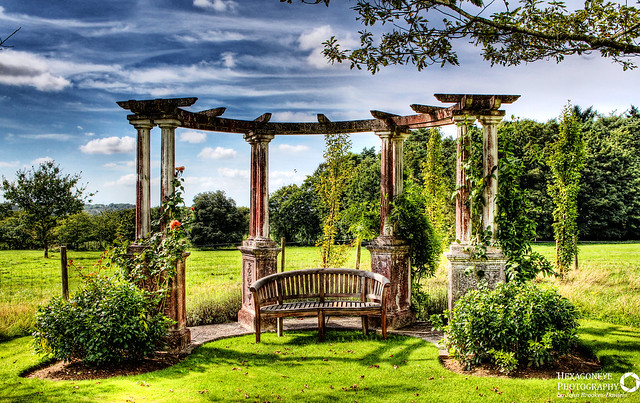 Beautiful Pergola at the bottom of the Garden at Hill Place, Swanmore.  The grandparents of the current custodians are buried under the Pagoda as they wanted to be together in their favourite place.  Hill Place is a grade II listed[ Georgian country villa located near the village of Swanmore in Hampshire, England. Richard Goodlad built Hill Place in about 1790. It is thought that Sir John Soane was the architect  In 2011, Hill Place was the subject of a Channel 4 television documentary presented by hotelier Ruth Watson as part of her Country House Rescue series.  Focal Length: 21 mm ISO Speed: 200 Aperture: f/11 Shutter Speed: 1/400 sec
