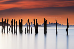 Boston Skyline through Decayed Pier at Sunset from Lovells Island in Boston Harbor (Greg DuBois - Sponsored by LEE Filters) Tags: gregdubois lovellsisland boston harbor islands skyline sunset decayed pier pilings surreal longexposure dreamscape leefilters bigstopper silhouette cloud movement motion water blur sea seascape cityscape urban northeast eastcoast newengland massachusetts north atlantic ocean calm serene waterscape aquatic coast coastline summer canon 6d sky dark dramatic moody orange red purple silver telephoto nautical photo photos stock photography photographer wallart