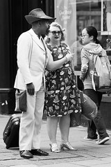 It's rude to point... (sawyersource) Tags: streetphotography street people person blackwhite bw blackandwhite brighton uk gb britain feet point three 3 hand hat suitcase suit d7200 nikon sigma 105mm stare eyes looking look