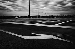 Tourner  gauche (Olivier DESMET) Tags: olivierdesmet noirblanc noiretblanc nb bw blackandwhite monochrome contraste highcontrast lowkey noir black texture parking street streetphoto streetphotography photosderue senart seinemarne 77 ricoh ricohgr gr 28mm fleche lignes ciel carresenart