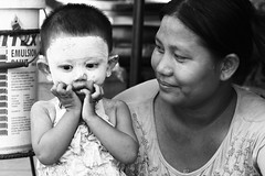 What has she done to ME! (Nomadic-Imagery) Tags: people blackandwhite woman monochrome face kid child faces head burma cream streetphotography peoples heads myanmar burmese cosmetic thanaka canoneos50d canon70200mmf4lislens