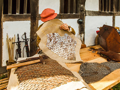 A member of the Tudor Group sews overlapping metal pieces onto cloth to make the 16th century style of armour known as 'Jack of Plates' (Anguskirk) Tags: uk history museum architecture rural westsussex eu oldbuildings c15 historic armor historical vernacular armour 2009 reenactment chichester singleton wealdanddownlandopenairmuseum bayleaffarmhouse wealdenhallhouse autumncountrysideshow 15thcenturywealdenfarmhouse tudorgroup jackofplates