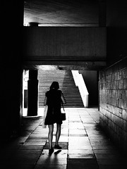 Walking on the South Bank (cycle.nut66) Tags: south bank london thames underpass woman silhouette light shade stairs concrete grainyfilmartfilter raised foot olympus epl1 evolt micro four thirds mzuiko