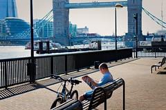 Sunworshipper (The Relevant Authorities) Tags: london wapping towerbridge man newspaper reading street bench rest break thesun tabloid cyclist bike bridge landmark cityhall theshard riverthames thames riverside