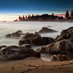 New Zealand Morning (Ed Kruger) Tags: ocean longexposure nightphotography morning blue trees winter sea newzealand sky sun seascape reflection beach water silhouette night clouds sunrise landscape early waves slow stones horizon wave sunny nz northisland kiwi aotearoa allrightsreserved 2012 neuseeland admiralty tauranga skyphoto nuevazelanda mountmaunganui nuovazelanda newzealandphoto edkruger photoofocean photoofnewzealand mtmounganui  abaconda qfse kirillkruger rodkruger photosofthesky     nightphotosofthesky