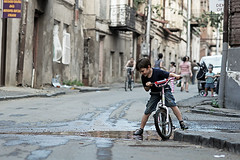 Boy on a bike stepping in a puddle in Tbilisi, Georgia (Simon Christiaanse) Tags: street city boy playing bike bicycle georgia children puddle dof capital streetphotography caucasus tbilisi sakartvelo   simonchristiaanse