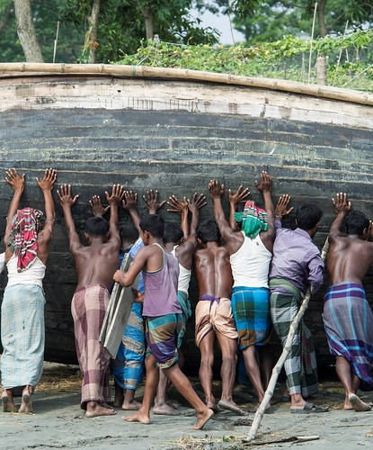 Fisher men lifting a boat in Bangladesh. Photo by Finn Thilsted