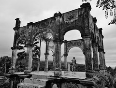 not quite alone (SM Tham) Tags: asia indonesia bali island karangasem amlapura tamanujong waterpalace watergardens gardenstosee building ruin folly pavilion columns arches reliefs decorations steps people blackandwhite monochrome outdoors trees plants