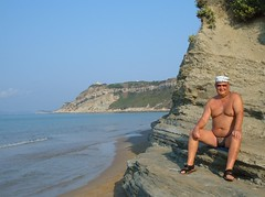 Corfu Arilllas PJ pauses on the way to the north beach (pj's memories) Tags: beach sunglasses seaside sandals greece brief corfu sunhat arillas tanthru kiniki
