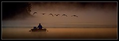 Inception of the Day (J Michael Hamon) Tags: widescreen boat man water lake pond morning dawn sunrise goose geese flock mood serene waterscape nature refuge muscatatuck indiana hamon nikon d3200 nikkor 55300mm photoborder silhouette scene scenery atmosphere