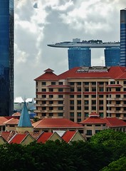 partial view of Marina Bay Sands (SM Tham) Tags: asia singapore holidayinnexpress clarkequay rooftop view artsciencemuseum marinabaysands buildings spire sky clouds trees outdoors