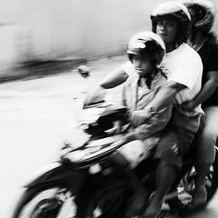 motobike trio. (Tobias Walter) Tags: street 2 blackandwhite bw bali blur contrast digital speed corner canon indonesia eos focus asia southeastasia dof mark grain streetlife scooter olympus 55mm ii rush tropical 5d 12 persons grainy zuiko oof motobike fastprime standartlens