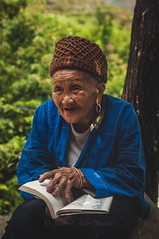 Let me tell you a story... (Syahrel Azha Hashim) Tags: paddyterrace nikon expression shallow holiday simple paddyfields details book highaltitude traditional guilin 50mm headgear mountain hat getaway handheld elder colorimage vacation reading prime light female naturallight traditionalclothing colorful terrain d300s travel syahrel dof moment colors china smiling longjipaddyterrace humaninterest detail