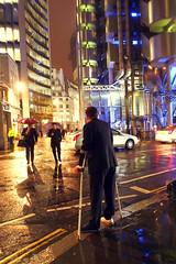 (Che-burashka) Tags: city man building london rain weather architecture night reflections evening loneliness kitlens crutches umbrellas lloyds bigcity badweather omd 1250 wetpavement em5 olympus1250mm