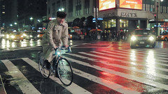 trenchcoat cyclist (Chee917) Tags: nyc newyorkcity night manhattan 34thstreet midtown macys 1320 28 digitalphotoprofessional canonpowershots100 iso2500