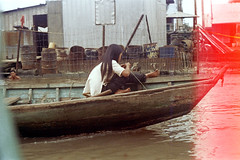 33-591 (ndpa / s. lundeen, archivist) Tags: nick dewolf nickdewolf 33 reel33 color photographbynickdewolf 1970s 1972 fall film 35mm winter 1973 asia vietnam southvietnam vietnamese southvietnamese saigon river saigonriver riverlife watersedge riversedge people building buildings house houses home homes woman youngwoman boat barefoot lightleak endroll endofroll endoftheroll