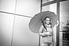 Waiting on the Rain to Stop (stimpsonjake) Tags: nikoncoolpixa 185mm streetphotography bucharest romania city candid blackandwhite bw monochrome woman umbrella rain waiting