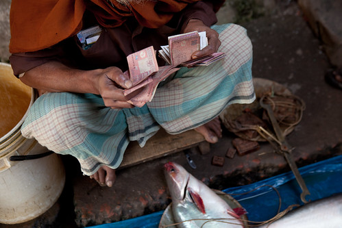 A fish seller counts his money at a small fish market in Khulna, Bangladesh. Photo by Mike Lusmore/Duckrabbit, 2012.