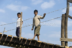 Boys wave to tourists from footbridge over river near Tonle Sap Lake. (dkjphoto) Tags: travel bridge boy lake fish tourism home water river boat fishing asia cambodia seasia cambodian tour village tide wave tourist siemreap stilt raised tonlesap