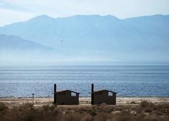 Salton Sea Showers (Spebak) Tags: california camping sky mountains bird beach clouds landscape haze wind flight brush ripples darkwater saltonsea beachbuildings lonebuildings