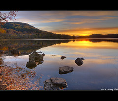 Loch Achray Sunrise (Kit Downey) Tags: morning autumn trees light mountain lake reflection fall water sunrise canon reflections lens landscape dawn scotland early october kiss rocks soft angle central wide scenic scottish peaceful super tokina kit loch tones f28 trossachs tranquil autumnal x4 downey achray 1116mm canoneos550d rebelt2i