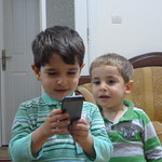 "Kerem plays with his dad's iPhone while Erdem looks on <a style=""margin-left:10px; font-size:0.8em;"" href=""http://www.flickr.com/photos/59134591@N00/8384482244/"" target=""_blank"">@flickr</a>"
