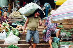 Smokng Man Carrying  Sack in Market, Surabaya Indonesia (AdamCohn) Tags: adamcohn indonesia pasarkeputran surabaya carrying cigarettesmoke man market marketplace sack smoking vegetables wwwadamcohncom