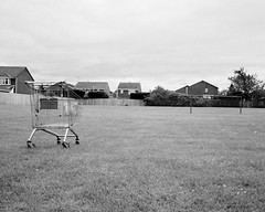 A Abandoned Shopping Trolley - Cramlington (Richard James Palmer) Tags: mamiya7ii mamiya 7ii 80mm ilford hp5 ilfordmicrophen microphen ishootfilm shoot film iso 400 iso400 ilfordhp5 f4 newcastle northeast north east street photography landscape black white rangefinder medium format 120 filmisnotdead analogue documentary epsonperfectionv700 epson v700 1125 landscapes newcastleupontyne upon tyne tyneandwear northern uk england urban melancholy art fineart new overcast isolated walkabout 2016 gritty gloomy trapped blackandwhite monochrome