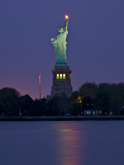 Our thoughts are with you - in explore (SunnyDazzled) Tags: city nyc longexposure nightphotography newyork reflection lady liberty newjersey purple flag flame torch statueofliberty libertyisland libertystatepark mygearandme