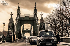 Hammersmith Bridge (Paki Nuttah) Tags: life city uk bridge england people white black west london cars car architecture walking mono blackwhite europe cityscape traffic walk taxi hammersmith gb flickrtravelaward