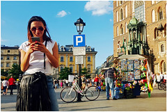 """""""Amused"""" - Krakow, Poland (TravelsWithDan) Tags: phone mobiledevice youngwoman amused smiling pretty krakow poland townsquare oldtown urban city flowerseller mobilephonephoto samsunggalaxys6 candid streetphotography"""