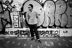 local man stands in front of graffiti wall with striped shirt (Benicio Murray) Tags: hp5 r09 oneshot fomafixp 35mm film blackwhite bw street man style graffiti tokyo japan travel stranger contax g2