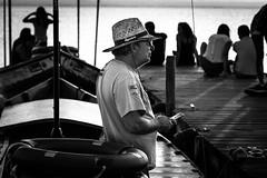 Gondolier (WhiteShipDesign) Tags: lake water boat travel contrast europe tourism beautiful story black white man person phone thinking dock gondola gondolier meditating nikon d7200