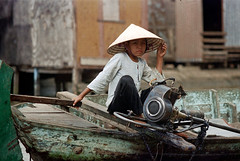 33-588 (ndpa / s. lundeen, archivist) Tags: nick dewolf nickdewolf 33 reel33 color photographbynickdewolf 1970s 1972 fall film 35mm winter 1973 asia vietnam southvietnam vietnamese southvietnamese saigon river saigonriver riverlife watersedge riversedge people building buildings house houses home homes stilts onstilts elevated builtonstilts woman youngwoman boat motor outboardmotor engine longtail longtailboat hat conicalhat traditionalhat girl