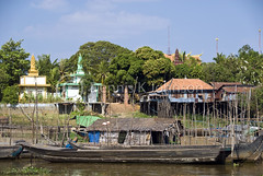 Fishing boats are moored riverside near Buddhist temples. (dkjphoto) Tags: travel lake fish tourism home water river temple boat fishing asia cambodia seasia cambodian tour village buddhist tide tourist siemreap stilt raised tonlesap