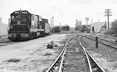 Seaboard Coast Line (former SAL) mainline view south toward the stations and diamond in downtown Plant City, Florida, mid 1970's (alcomike43) Tags: road street old blackandwhite bw classic station vintage ties switch photo diesel platform tracks engine historic negative photograph rails target depot locomotive siding ge spikes sal acl ballast generalelectric rightofway scl dieselengine 378 turnout mainline seaboardcoastline roadbed diesellocomotive gradecrossing branchline dieselelectriclocomotive atlanticcoastline plantcityflorida seaboardairline u18b switchstand tieplates anglebars fredclarkjr conventionaljointedsectionrails dwarfblocksignal 1964chevroletstationwagon
