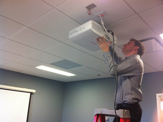 A technician installs a projector in a new conference room at the Arlington Heights Memorial Library