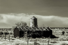 Toonerville (Not the Trolley Barn) (unknown quantity) Tags: fence clouds weathered noroof scrubbrush rust silo abandoned horizon deadtrees infrared pasture neglected oxidation fadedpaint cloudsstormssunsetssunrises monochrome corrugatedmetal exposedwood landscape hss
