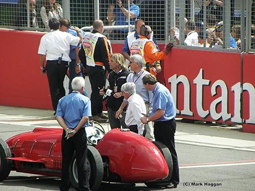 Bernie Ecclestone watches Fernando Alonso drive a historic Ferrari at the 2011 British Grand Prix