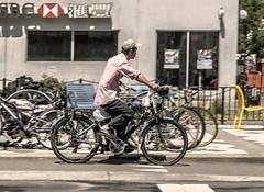 Biking In Manhattan (nrhodesphotos(the_eye_of_the_moment)) Tags: dsc01736160 theeyeofthemoment21gmailcom wwwflickrcomphotostheeyeofthemoment candid bicycle biker reflections shadows transportation manhattan windows glass sign display metal bikerack outdoor streetscene man peddling nyc curb vehicle bike store chairs people facebook