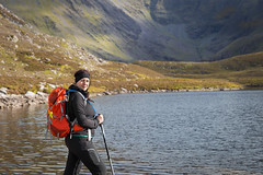 Female trekker posing lake side in the mountains (Semmick Photo) Tags: black blue carrauntoohil clouds devonian female hewitts ireland lake lougheagher macgiollamochuda macgillycuddy macgillycuddysreeks mountains nature orange sky walking water woman action active adventure background backpack beautyinnature countryside day gear healthy hiker hiking hillside irish jacket kerry landscape mountainrange outdoors pants peaks poles rural scenery scenic smiling sticks trekking valley view yellow
