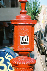 LOVE ME (janniswerner) Tags: street new york city nyc newyorkcity red urban ny newyork streets love film sign analog canon eos 50mm sticker cityscape post 5 50mm14 a2e
