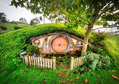Another Perfect Little Hobbit Hole (Stuck in Customs) Tags: newzealand northisland stuckincustomscom treyratcliff treyratcliffcom hobbiton matamata waikato nz ratcliff trey horizontal houses hobbit lordoftherings lotr pub greendragoninn inn colour color outside outdoor outdoors mirror reflection lake pond water light glowing underground trees blue purple white black orange green yellow hills rolling rr dailyphoto sony ilce7r may 2016 p2016 home garden flower plant flowerbed ilce7rm2