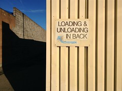 Getting Loaded (misterbigidea) Tags: street city blue roof shadow sky urban signs building brick rooftop lines sign metal wall corner dark point landscape back alley view pointer front business ribs directions arrow pointing stockton zone loading ridges sides unloading