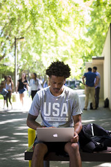 Justin Herbert, a senior studying criminal justice, sits in front of Mariposa Hall and orders his book rentals online. (Sac State) Tags: public affairs california state university sacramento vernone sacstate sacramentostate calif usa us