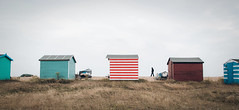 Solitary (V Photography and Art) Tags: beachhuts lines stripes huts beach grass sky wind weather stark boats redandwhite blue bythesea canon scale silhouette life