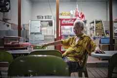 This old man is Apek. (framptoP - E.V.I.L. Photographer) Tags: owner shop shopkeeper face portrait one place indoor wear chinese man old adult table chair places