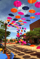 Festive Umbrellas (Tom Mortenson) Tags: wisconsin wausau colorful umbrellas digital outdoors centralwisconsin suspended usa midwest colors canon canon6d canoneos street downtown festive america northamerica lighterthanair geotagged whimsical colours parasols pattern colourful 24105l bright marathoncounty wausauwisconsin brightcolors